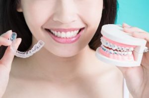 Woman holding a clear tray and braces