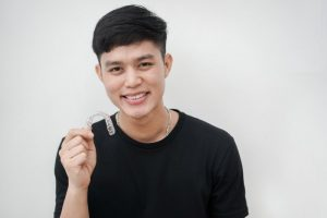 young man smiling holding invisalign tray